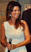 Shania Twain wearing a white dress is standing holding a microphone and smiling.