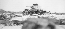 A white, destroyed tank stands on the snow.