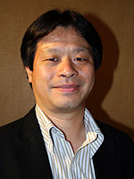 A 42-year-old Japanese man with trimmed black hair, smiling directly at the camera.