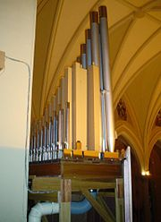 The organ of St Raphael's Cathedral in Dubuque, Iowa, showing some pipes, the interior of the case, and part of the wind system