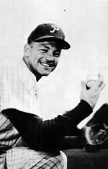 A black and white image of a smiling man in a baseball uniform holding a baseball