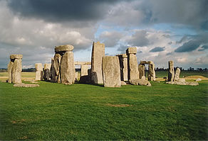 Standing stones at Stonehenge in the sunlight, with dark clouds above