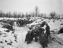In the foreground, a group of soldiers huddle in a group in a snow-covered trench. Another group stand in the background.