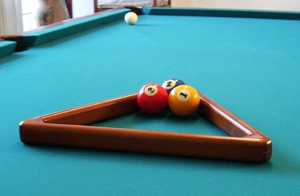 Racking a game of three-ball with the standard fifteen-ball triangle rack. [taller view] Three-ball rack in std triangle 1a.jpg