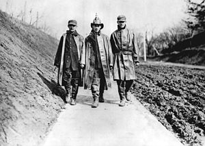 Toronto Fire Services - Three firefighters walk beside muddy Lansdowne Avenue, north of Davenport Road, c. 1911