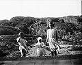 Tre flickor iklädda klänningar håller varandra i handen på strand. Troligen i Fiskebäckskil, Bohuslän - Nordiska Museet - NMA.0054136.jpg