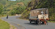 Zwei Radfahrer halten sich an der Rückseite eines Lastwagens fest, der einen Hügel hinunterfährt