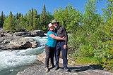 Two hikers affectionately posing in front of the Gamájåhkå rapids in Kvikkjokk, Sweden (DSCF2456).jpg
