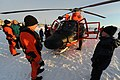 U.S. Coast Guard Petty Officer 2nd Class Chad Griffin, an aviation mechanic, speaks to a Nome, Alaska, resident about working aboard a Coast Guard MH-65 Dolphin helicopter in Nome Jan 120118-G-YE680-099.jpg