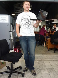 In a cavernous convention centre of industrial design demarcated with temporary office partitions, a man with a goatee and close-cropped brown hair and earphone buds is standing, holding an open laptop in his left hand. His right hand, except for his thumb, is in the pocket of his blue jeans, and he wears a white T-shirt with the signature and three-quarter profile outline of Esperanto founder L.L. Zamenhof, a friendly, full-bearded but balding man with a prominent nose and round glasses. Behind him is a circular staircase; to his left two women are in conversation.