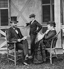 President Grant and family pose in an informal portrait outside. Grant is seated to the left and his wife Julia is seated to the right. Their son Jesse is standing between Grant and Julia.