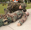 US Navy 031003-N-2923W-003 Hospital Corpsman 2nd Class Bobby Ferrell applies Emergency Medical Technician (EMT) skills to a simulated unconscious patient during a mass casualty drill.jpg