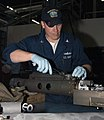 US Navy 040427-N-5274S-004 Gunner's Mate 2nd Class William Eversmann applies safety wire to a 25mm machine gun at Naval Station Everett's Industrial Maintenance Facility Ordnance-Fire Control shop.jpg