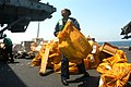 US Navy 040730-N-7569S-003 Store Keeper Seaman Christie Brown of Oxford, Miss., helps move 13-thousand pounds of mail aboard the aircraft carrier USS John F Kennedy (CV 67).jpg