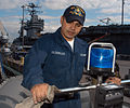 US Navy 050324-N-3390M-154 Seaman Allan Calzadillas, assigned to guided missile destroyer USS Momsen (DDG 92), cleans the law enforcement light system aboard one of the ship's seven-meter Rigid Hull Inflatable Boats (RHIB).jpg