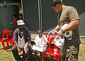 US Navy 070815-N-9421C-136 Hospitalman John Dahilig, attached to 3rd Medical Battalion, gives a young boy a soccer ball and flag while they wait to see medical personnel at Miak Health Clinic during a medical civic action progr.jpg