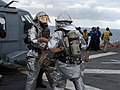 US Navy 071106-N-1786N-062 Crash and salvage personnel rescue a simulated casualty during a flight deck fire drill aboard amphibious assault ship USS Tarawa (LHA 1).jpg