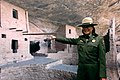 US Navy 071215-N-2038L-002 Park Ranger Tessy Shirakawa, a park ranger at Mesa Verde National Park, points to a large photographic panoramic display of early Mesa Verde cliff dwellings.jpg