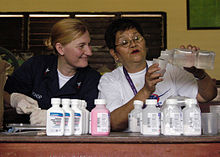 US Navy 090527-N-7415V-003 Hospital Corpsman 2nd Class Katherine Bishop watches pharmacist Teresa Balcos prepare medication for a medical mission at Bang Bang Elementary School.jpg