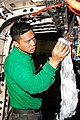 US Navy 100222-N-3327M-029 Aviation Machinist's Mate 2nd Class Raynard Eugenio, assigned to the Warhawks of Strike Fighter Squadron (VFA) 97, performs maintenance on the engine of an F-A-18C Hornet aboard the aircraft carrier U.jpg