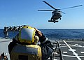 US Navy 100421-N-1559J-002 Boatswain's Mate 1st Class Chuyi Chang directs an SH-60B Sea Hawk helicopter, from Helicopter Anti-submarine Squadron (HS) 46, onto the flight deck of the guided-missile destroyer USS Laboon (DDG 58).jpg