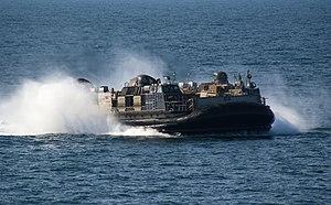 US Navy 120207-N-PB383-656 A landing craft air cushion assigned to Assault Craft Unit (ACU) 5 approaches the welldeck of the amphibious transport d.jpg