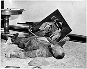 With a torn picture of his Führer beside his clenched fist, a dead general of the Volkssturm lies on the floor of city hall, Leipzig, Germany. He committed suicide rather than face U.S. Army troops who captured the city.