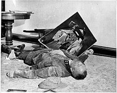 Photo noir et blanc prise le 19 avril 1945, à l'intérieur d'un bureau de l'hôtel de ville de Leipzig. Sur le sol, un homme mort, en uniforme, est allongé de tout son long, sa tête vers la droite au premier plan. Un mur blanc forme l'arrière-plan de la photo. Au second plan, entre une chaise renversée le long du mur et le flanc droit du cadavre, tient en équilibre un portrait d'Adolf Hitler dont le visage a été lacéré.