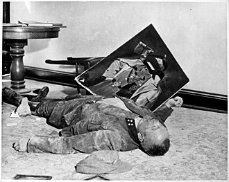 Mass suicides in 1945 Nazi Germany - The body of Volkssturm Bataillonsführer Walter Doenicke lies next to a torn portrait of Hitler. Doenicke committed suicide in the city hall, Leipzig, Germany shortly before the arrival of allied troops on 19 April 1945.