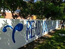 """Opiskelijaelämän logo ja """"lue paikallislehteäsi"""" -viesti, maalattu sinisellä valkoista taustaa vasten Walker Wall -lehdelle"""