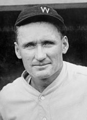 "A shoulders-up picture of a smiling man in a white baseball uniform. He is wearing a dark-colored baseball cap on his head with a white block ""W"" on the front."