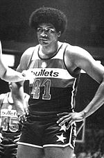 "A black-and-white photo of a black man wearing a red, white, and blue uniform that says ""Bullets"" on it with the number 41 worn."