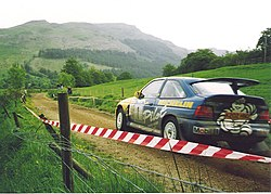 A Ford Escort Cosworth on a stage rally, driven by British driver Malcolm Wilson.