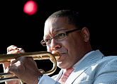 An African-American male playing a trumpet. He is wearing glasses and a light blue suit.