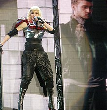 Madonna in a robotic outfit standing in front of a video screen.