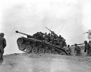 Men sit on a tank which is holding position among a line of troops