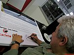 """Academia da Força Aérea (AFA) em Pirassununga-SP-Brasil. O primeiro astronauta brasileiro, o bauruense Marcos Pontes dando um autógrafo em um banner no Domingo Aéreo 2015 no """"Ninho das - panoramio (1).jpg"""