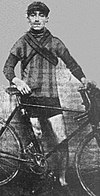 A male cyclist standing next to his racing cycle