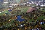 Luftfoto av den midtre delen av parken med rosenhagen, Grüttsee og de beskyttende skogene i Tiefenbrunnen.  Helt til høyre i utkanten av bildet: vannverket