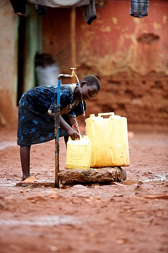Water supply - A young girl collects clean water from a communal water supply in Kawempe, Uganda.