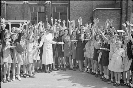 Food aid from America: British pupils wave for the camera as they receive plates of bacon and eggs. Aid From America- Lend-lease Food, London, England, 1941 D4324.jpg