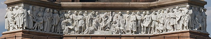 "A face of the high-relief Frieze of Parnassus round the base of the Albert Memorial in London. Most of the heads and many feet are completely undercut, but the torsos are ""engaged"" with the surface behind. Albert Memorial Friese Facing South - May 2008.jpg"