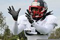 Alex Collins, a running back with the East Coast Team of the Semper Fidelis All-American Bowl, puts his hands up to catch a pass during the second day of practice aboard Fullerton College Football Field 130101-M-EK802-494.jpg