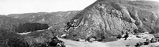 Black and white panoramic view of a canyon, a group of trees is to the left and several residential buildings are at lower right.