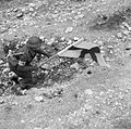 An RAMC medical orderly makes his way forward under cover of the Red Cross flag to recover a casualty during fighting at Cassino, 24 March 1944. NA13276.jpg