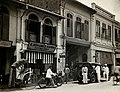 An arcade of shops with a road sweeper at work in the street of Kuala Lumpur, 1915-1925.jpg
