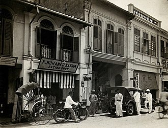 An arcade of shophouses with a road sweeper at work in the street of Kuala Lumpur, c. 1915-1925. An arcade of shops with a road sweeper at work in the street of Kuala Lumpur, 1915-1925.jpg