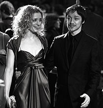 A black and white image of a blonde women wearing a stain dress and dark-haired male standing beside each other. She is looking to her left and holding a clutch purse with her right hand. He is wearing an all black suit and smiling.