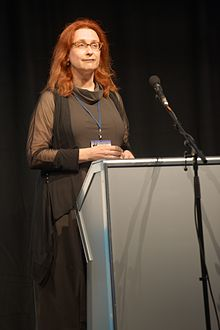 Photograph of Audrey Niffenegger standing behind a lectern, delivering the inaugural PEN/H.G. Wells lecture at Loncon, Worldcon 2014