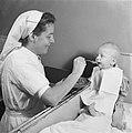 Baby wordt gevoerd door verpleegster, Bestanddeelnr 900-7969.jpg